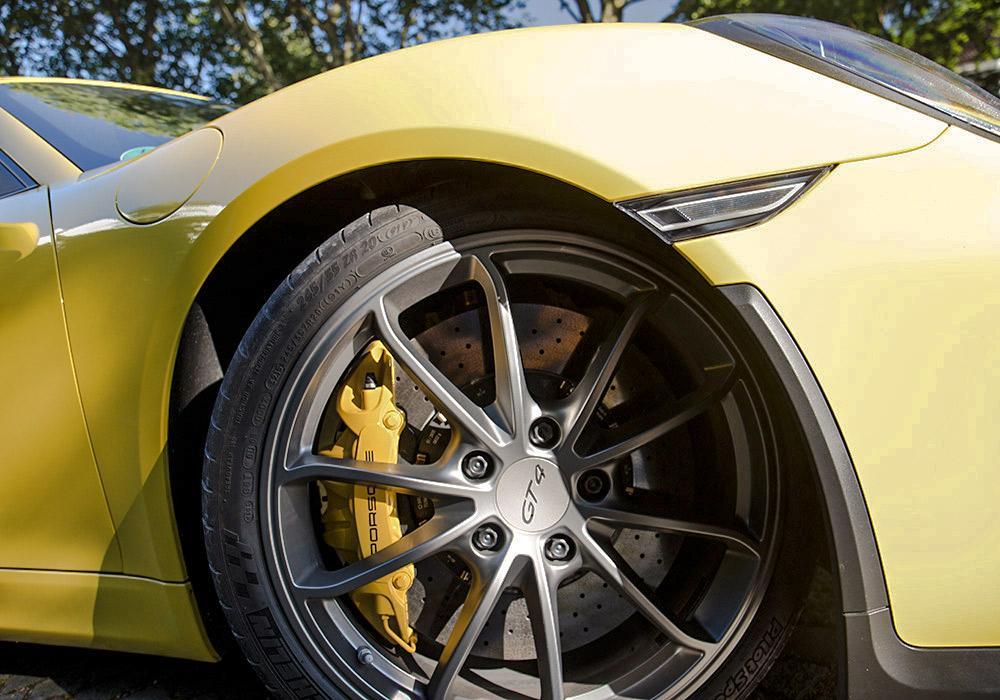 Rechtes Vorderrad eines gelben Porsche Cayman GT4