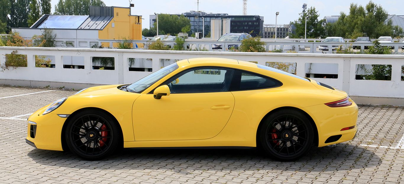 Porsche 911 Carrera GTS gelb Seitenansicht links geparkt