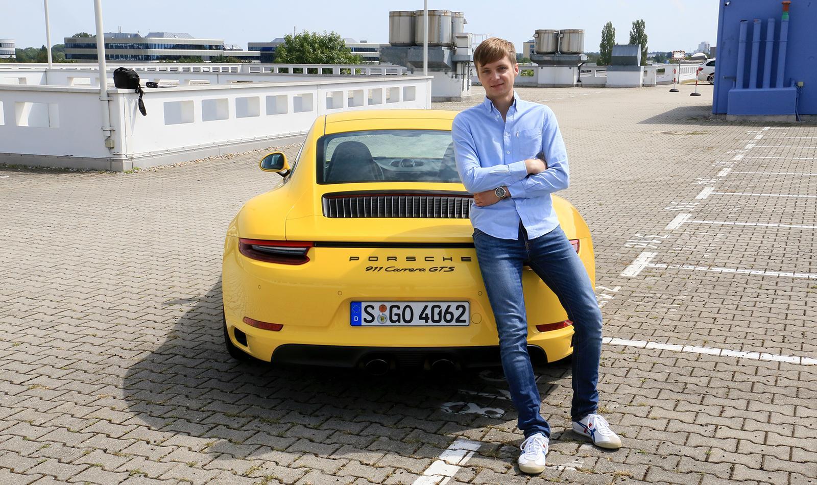 Porsche 911 Carrera GTS gelb Heckansicht mit Redakteur auf Motorhaube lehnend