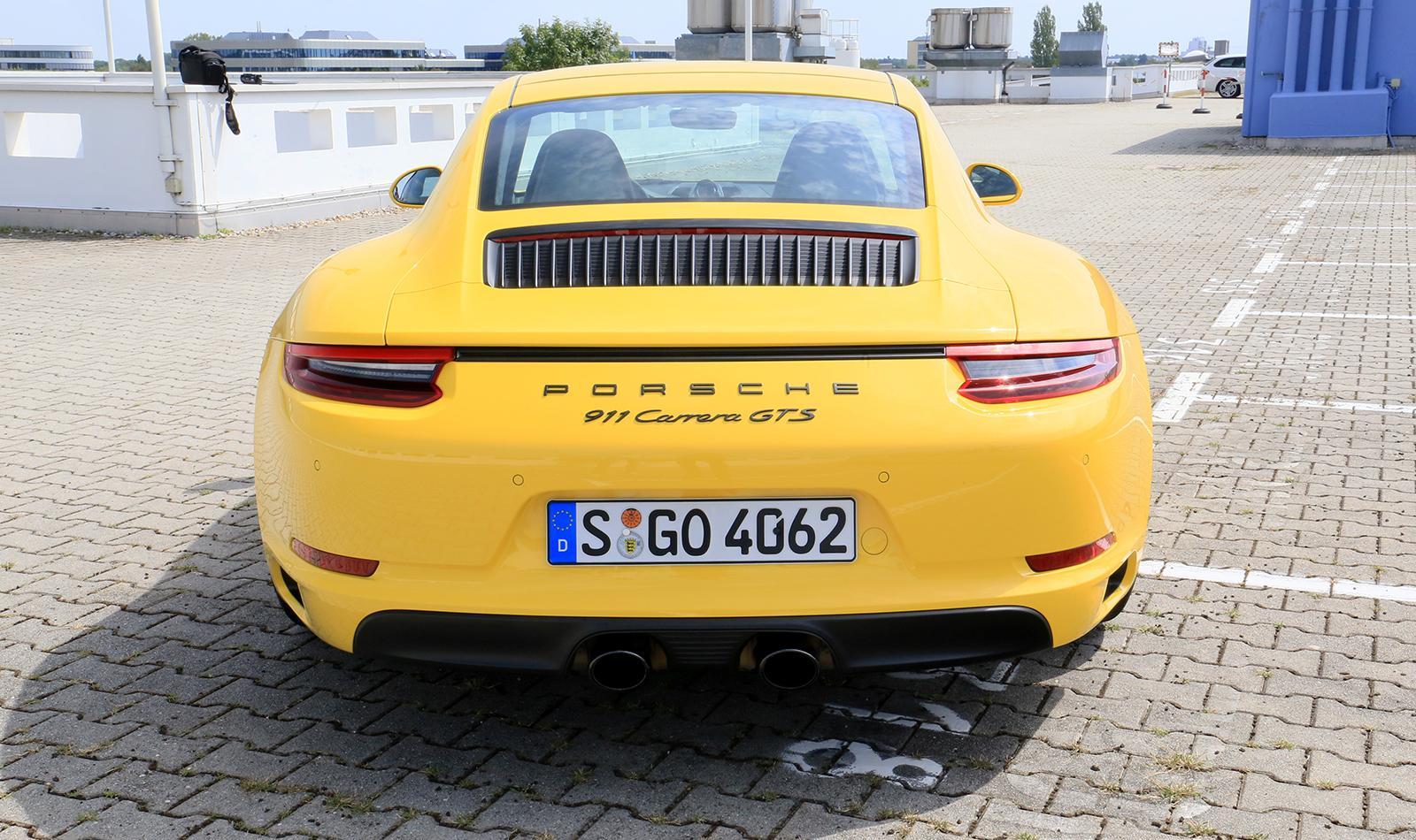 Porsche 911 Carrera GTS gelb Heckansicht parkend
