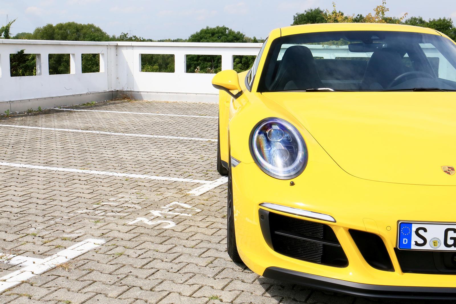 Porsche 911 Carrera GTS gelb halbierte Frontansicht rechts vorne parkend Parkplatz