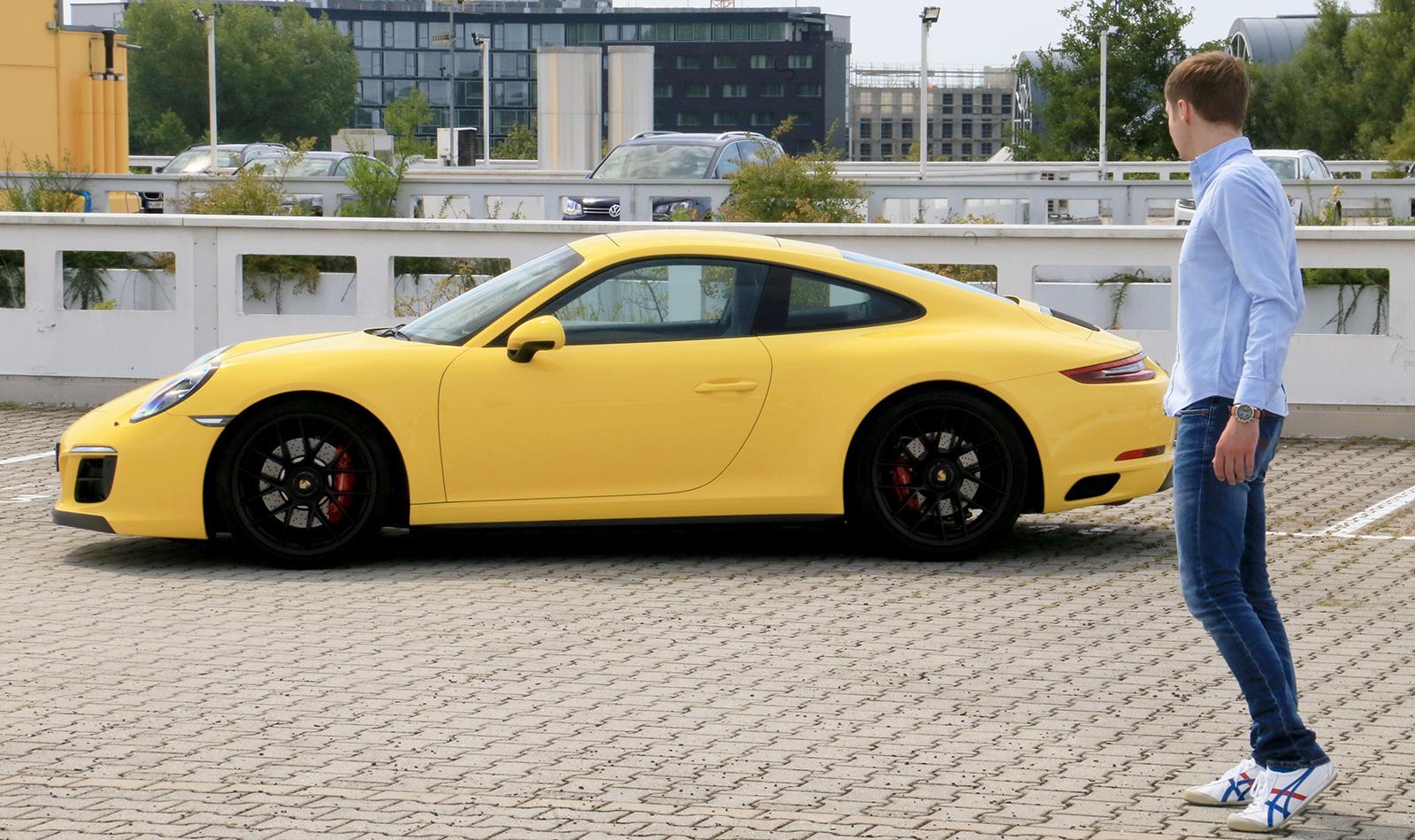 Porsche 911 Carrera GTS gelb Seitenansicht parkend Redakteur geht los zum Einsteigen