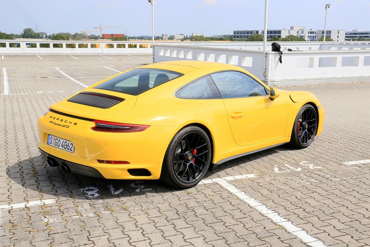 Porsche 911 Carrera GTS schräg rechts hinten gelb parkend