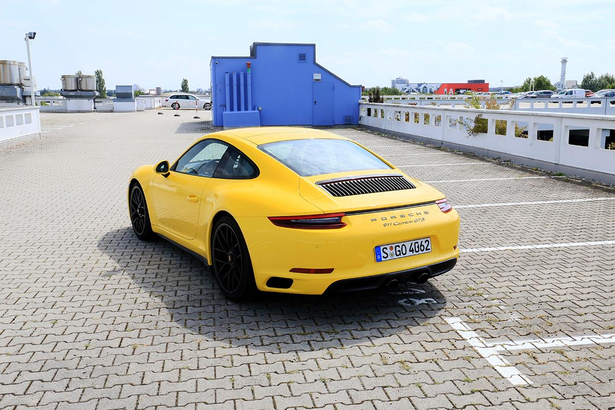 Porsche 911 Carrera GTS gelb parkend schräg links hinten