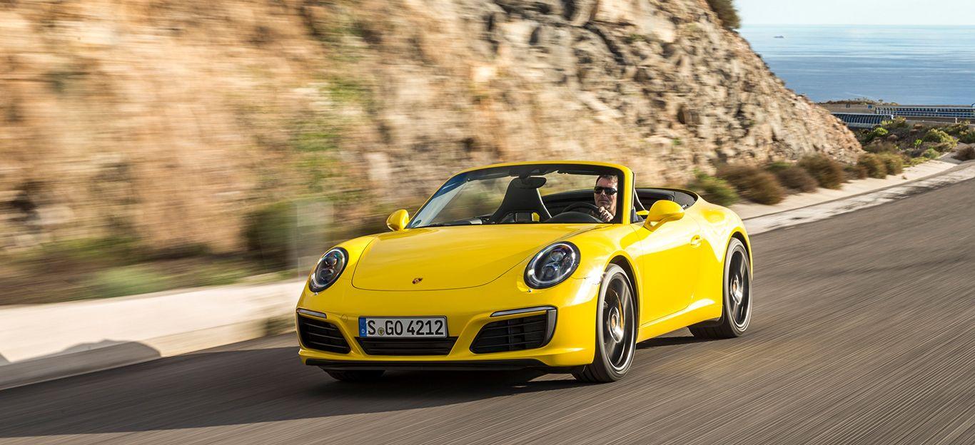 Porsche 911 Carrera S Cabriolet gelb schräg links vorne auf Küstenstraße fahrend