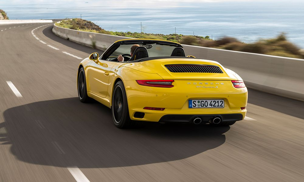 Porsche 911 Carrera S Cabriolet gelb schräg links hinten auf Küstenstraße fahrend