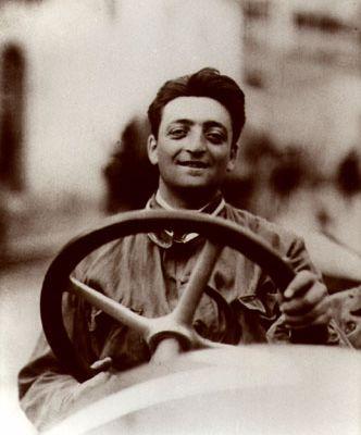 Enzo Ferrari, in jungen Jahren, sitzt auf diesem Sepiafoto lächelnd hinter dem großen Lenkrad eines nicht im Bild sichtbaren Autos