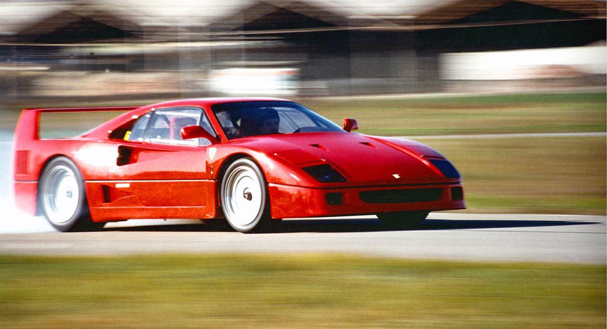 Ferrari F40 auf Rennstrecke fahrend schräg rechts vorne, Hintergrund in Bewegungsunschärfe