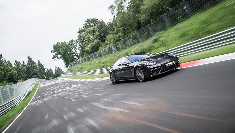 Porsche Panamera Turbo auf der von Fans beschrifteten Nordschleife fahrend, schräg rechts vorne