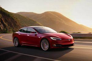 Ein roter Tesla Model S auf einer Landstraße.