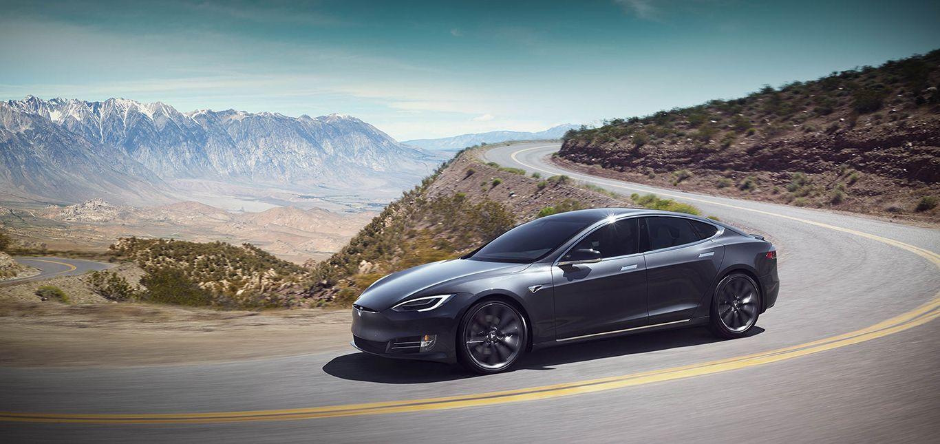 Tesla Model S auf kurviger Bergstraße, Prärie im Hintergrund