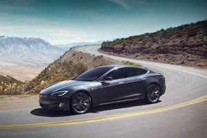 Tesla Model S auf Serpentinenstraße, Prärie im Hintergrund
