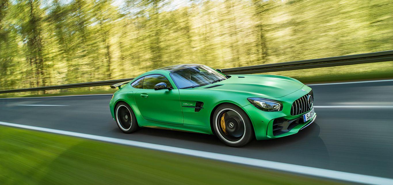 Grüner Mercedes AMG GT R schräg seitlich vorne fährt durch Wald
