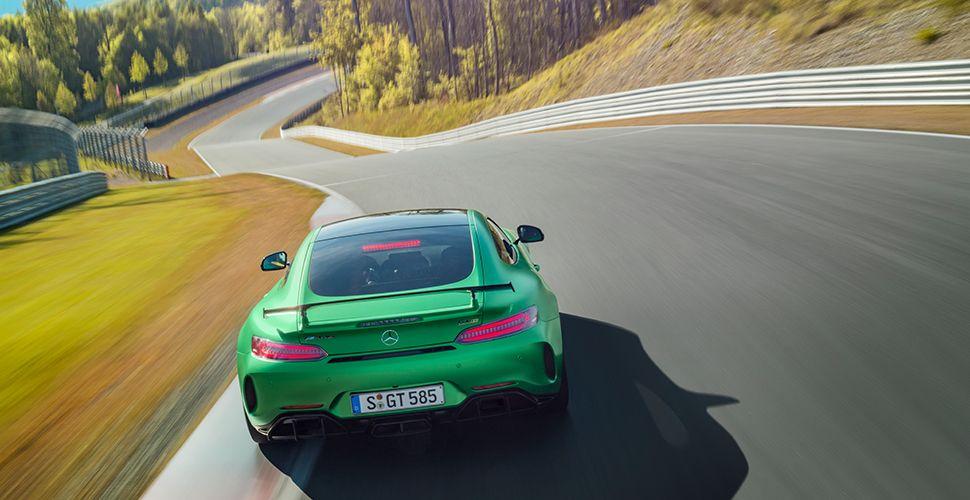 Grüner Mercedes AMG GT R von hinten fotografiert auf der Rennstrecke durch eine langgezogene Linkskurve fahrend