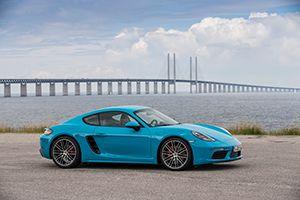 Porsche 718 Cayman miamiblau in Schweden vor Brücke übers Meer geparkt