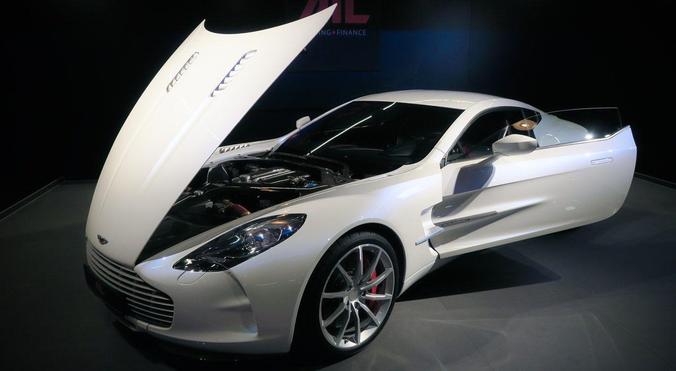 Weißer Aston Martin One-77 mit geöffneter Fahrertür und Motorhaube schräg links vorne