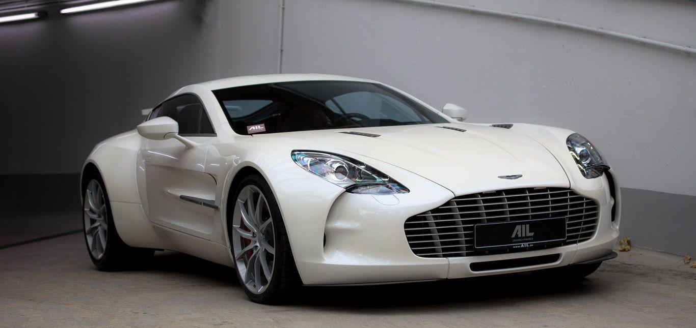 Der Aston Martin One-77 (Nr. 67) in weiß vor einer Garagenauffahrt.