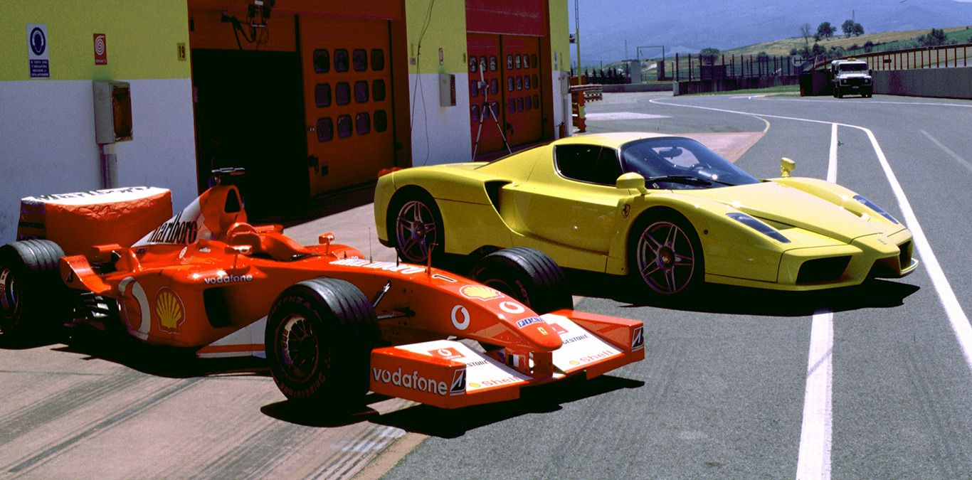 Ein gelber Ferrari Enzo neben dem Formel 1 Auto von Michael Schumacher.