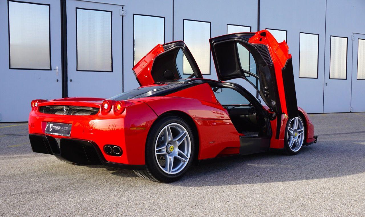 Roter Ferrari Enzo Ferrari von schräg rechts hinten mit offenen Flügeltüren vor Lagerhalle