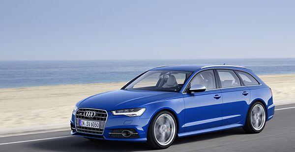Blauer Audi S6 Avant fahrend am Meer, Sandstrand schräg links vorne