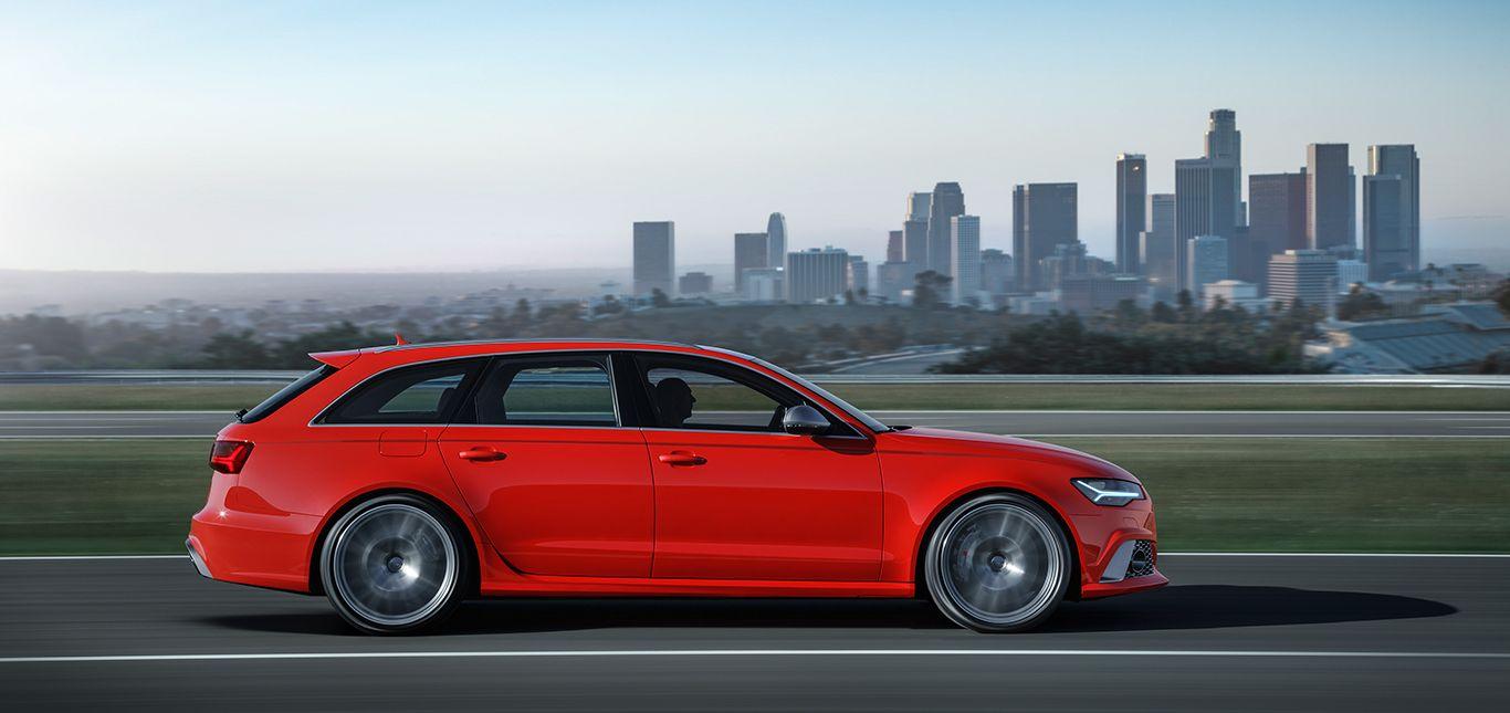 Audi RS6 Avant rot fahrend Seitenaufnahme Hochhaus-Skyline im Hintergrund