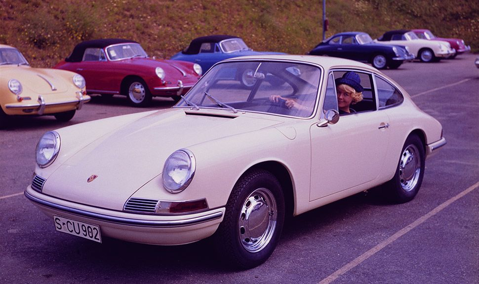 Weißer Porsche 911 Urtyp stehend vor einer Reihe 356er