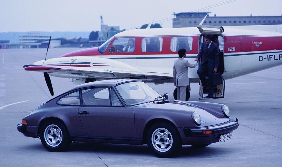 Frühes Porsche 911 G-Modell auf Rollfeld vor aus einer Propellermaschine aussteigenden Geschäftsleuten