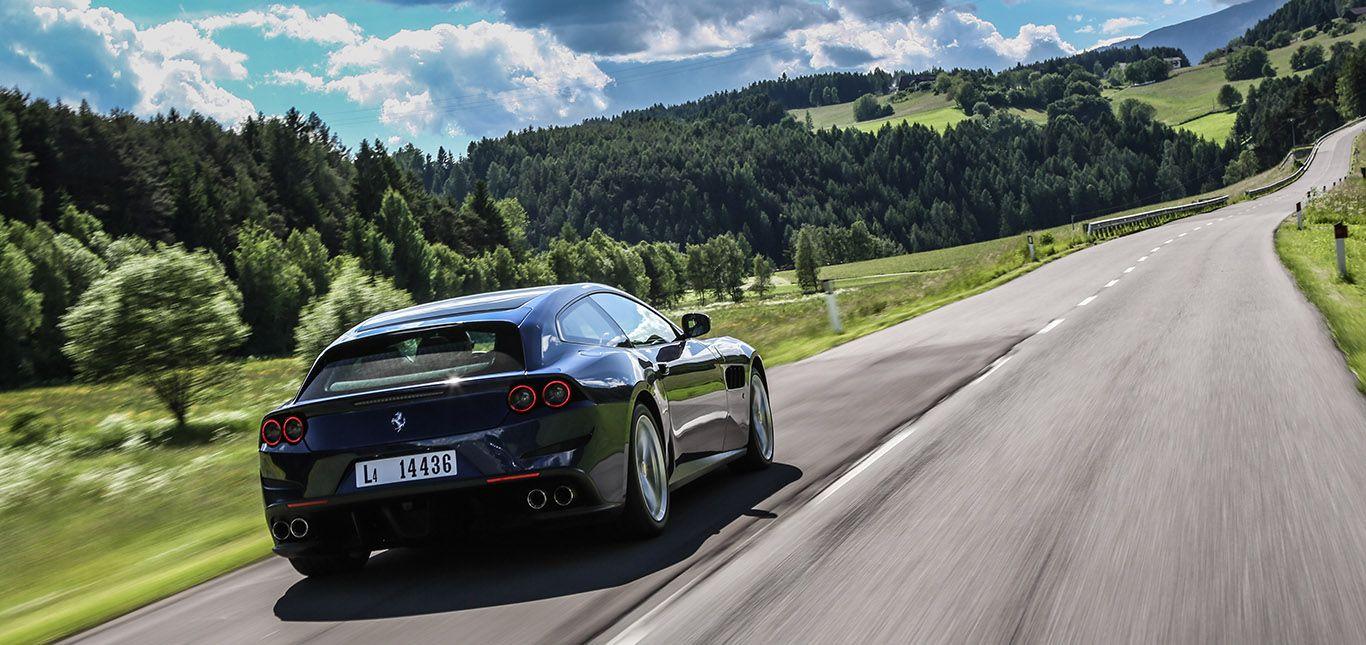 Dunkelblauer Ferrari GTC4Lusso fährt auf Landstraße mit sattem Baumgrün und weiß-blauem Himmel