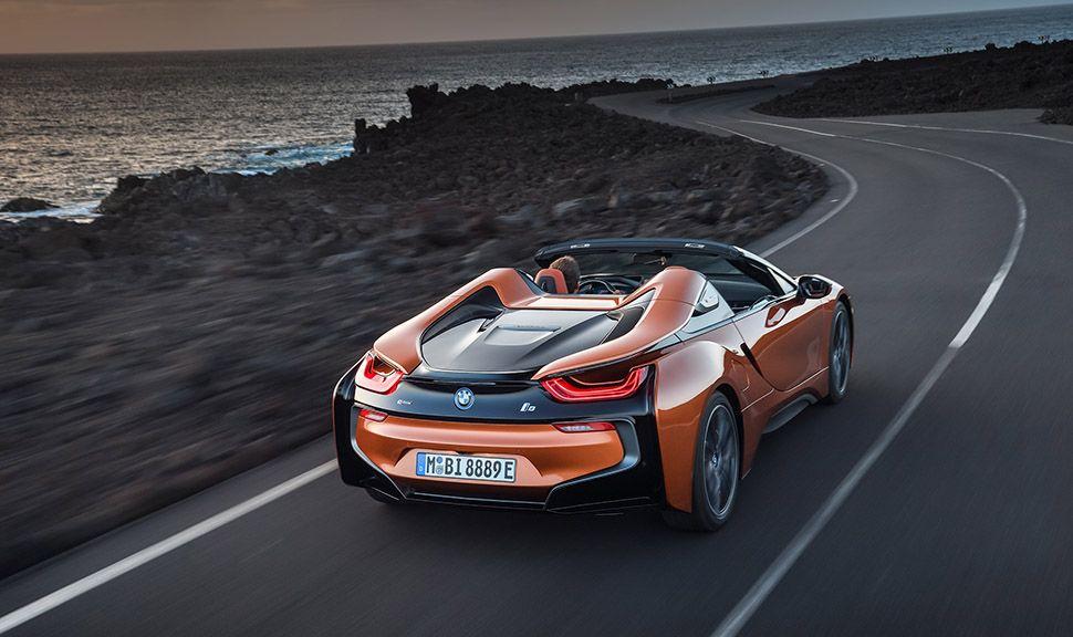 BMW i8 Roadster in orange auf Küstenstraße fahrend
