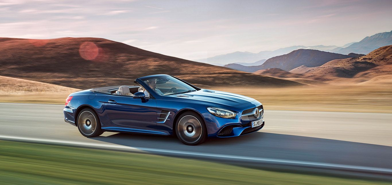 Mercedes SL 500 brilliantblau offen fahrend Dämmerung
