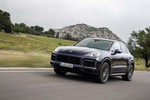 Porsche Cayenne E-Hybrid schräg links vorne auf Landstraße fahrend