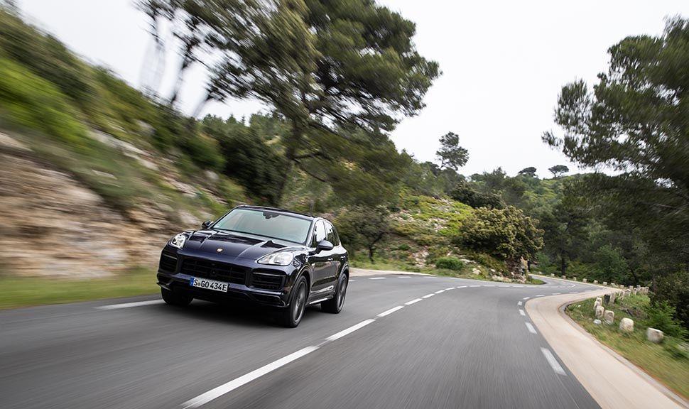 Porsche Cayenne E-Hybrid von vorn auf Landstraße fahrend
