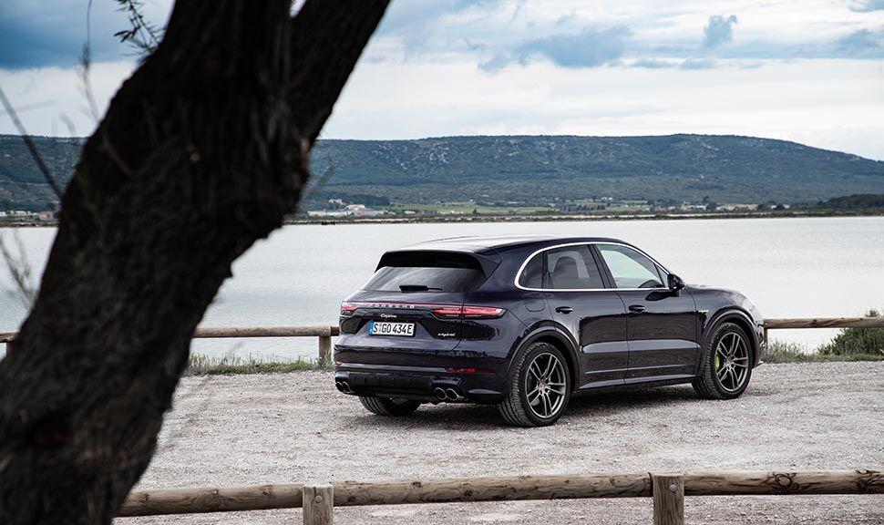 Porsche Cayenne E-Hybrid am See geparkt schräg rechts hinten