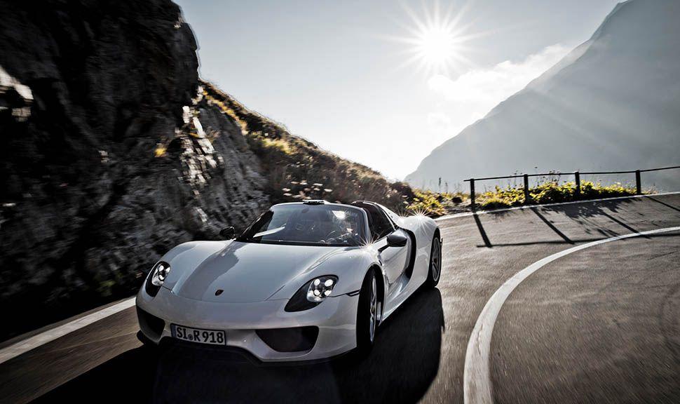 Porsche 918 Spyder auf Alpenstraße mit Sonne im Hintergrund