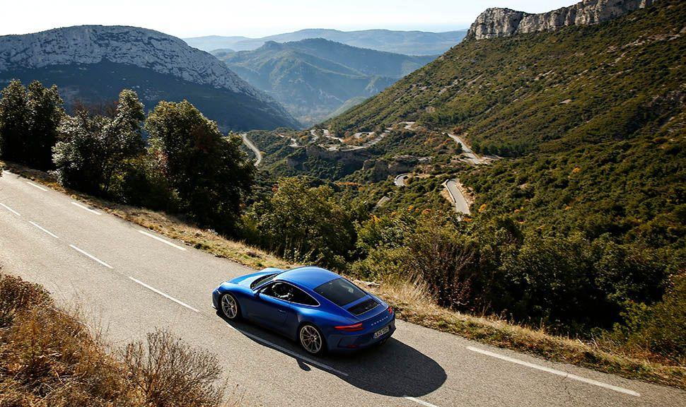 Porsche 911 GT3 Touringpaket Blau auf Bergstraße schräg links hinten seitlich versetzt, fahrend