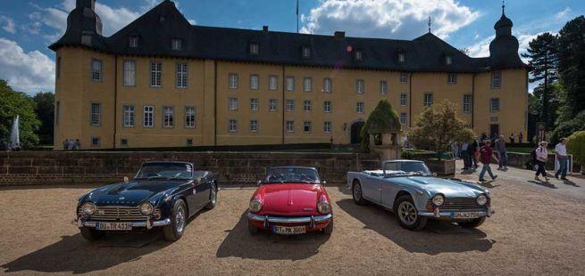 3 Oldtimer vor dem sommerlichen Schloss Dyck