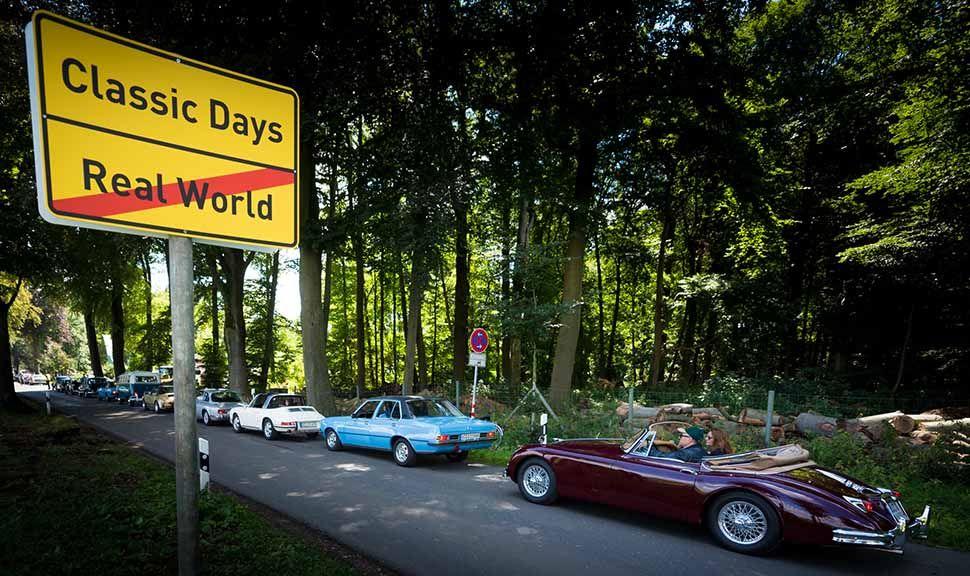 Oldtimer fahren auf Allee zu den Classic Days auf Schloss Dyck, Ortsschild
