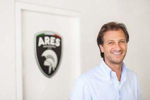 ARES Chef Dany Bahar lachend vor Firmenlogo