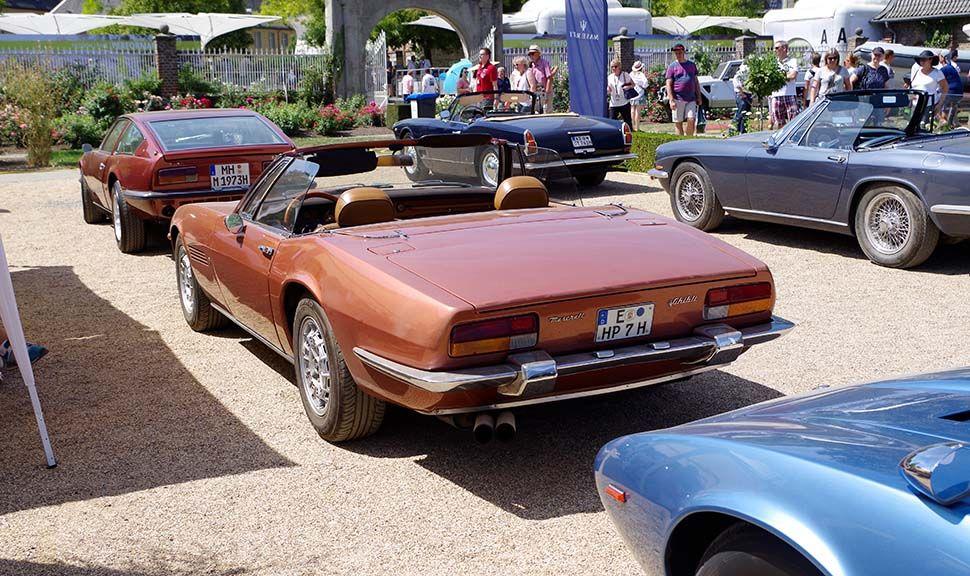 Bronzebrauner Maserati Ghibli Spyder mit offenem Verdeck links hinten