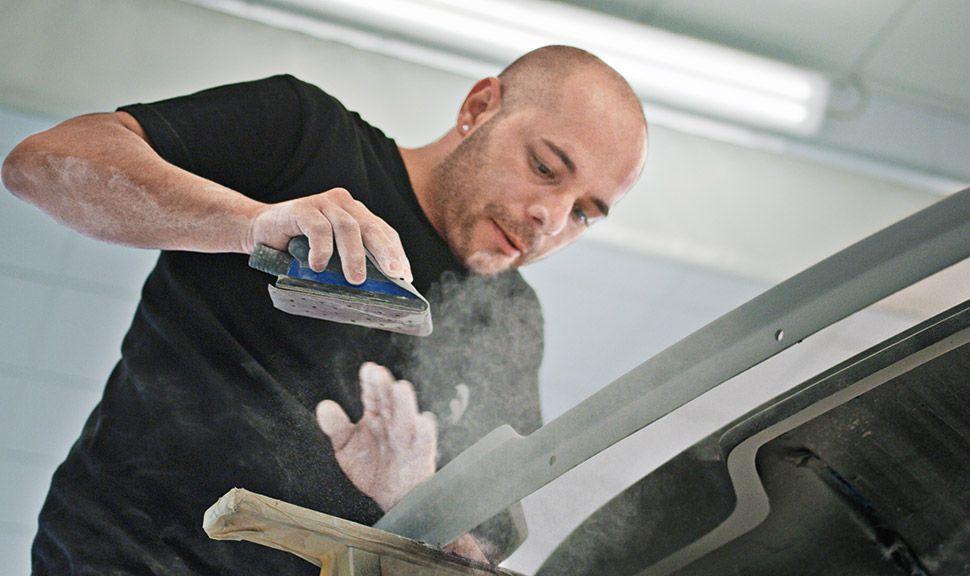 Arbeiter schleift per Hand ein Werkstück