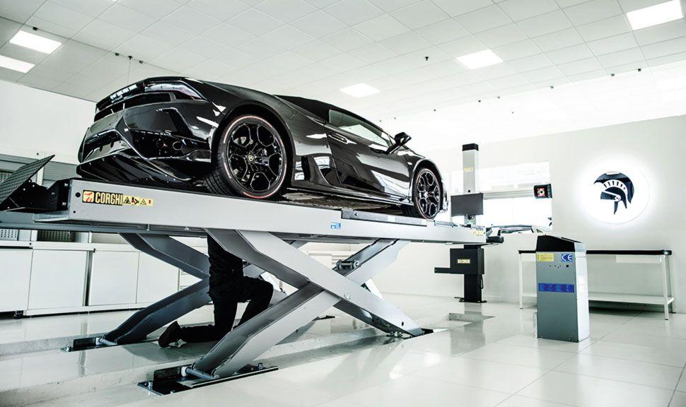 Schwarzer Lamborghini auf Hebebühne in ARES Design Fabrikhalle
