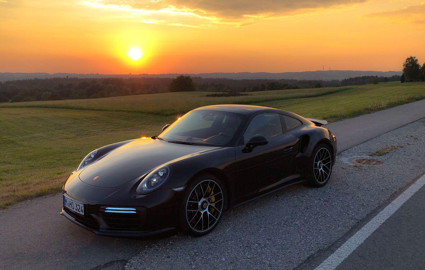 Porsche 911 Turbo S schräg links vorne auf Landstraße im Sonnenuntergang