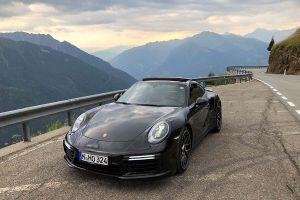 Porsche 911 Turbo S auf Passstraße mit Bergpanorama schräg links vorne