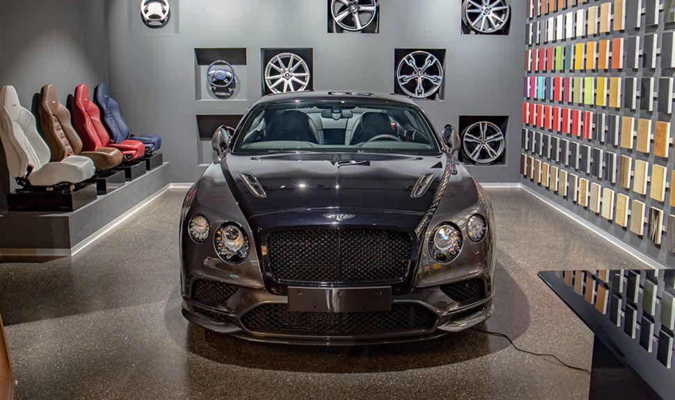 Bentley Continental im Showroom von Scuderia Motors vor bunten Sitzen, Felgen und einer Farbpalette