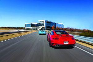 Roter Porsche 911 Turbo und miamiblauer 911 fahren auf Strecke des Porsche Experience Center Atlanta