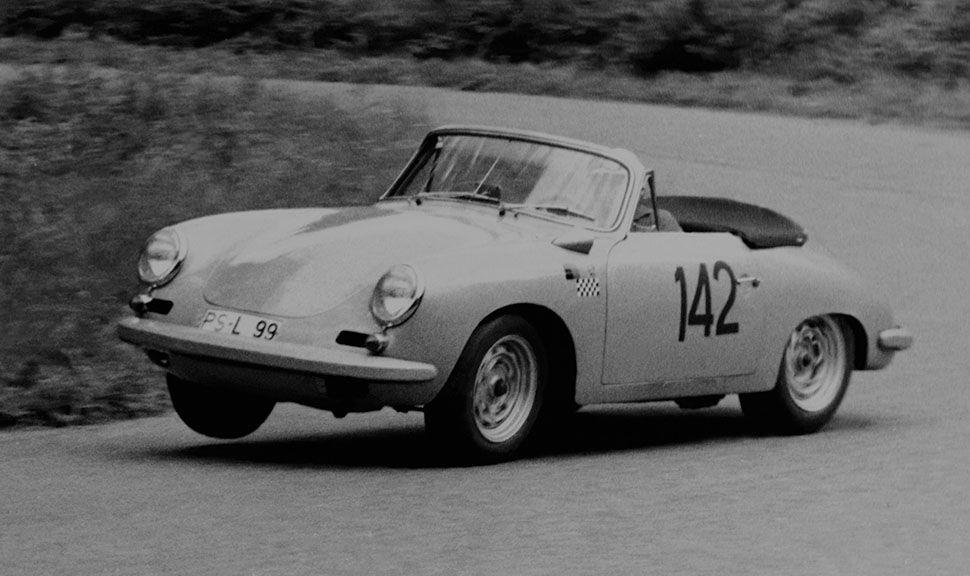 Schwarz-Weiß-Foto eines Porsche 356 B Carrera 2 Cabrios mit Startnummer 142 auf Tür, fährt im Renntempo driftend durch Kurve