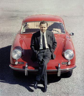 Ferry Porsche im Anzug auf der Motorhaube eines roten Porsche 356 Coupé lehnend