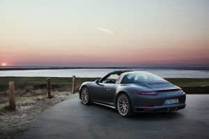 Porsche 911 Targa 4 GTS Exclusive Manufaktur Edition an Sylter Küste im Sonnenuntergang stehend schräg links hinten