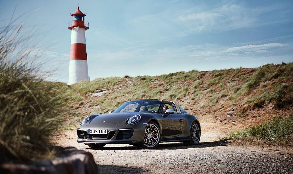 Porsche 911 Targa 4 GTS Exclusive Manufaktur Edition parkt vor Leuchtturm im Hintergrund auf Sylt
