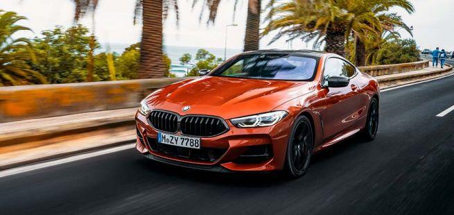 BMW M850i Orange schräg links vorne auf Palmenallee fahrende